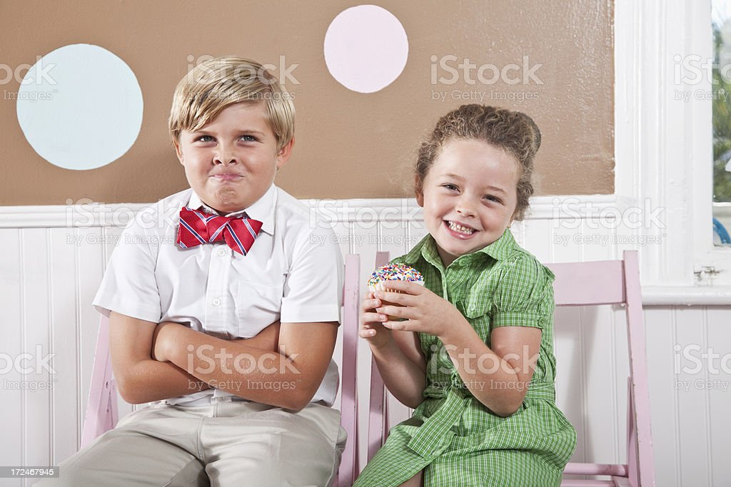 Boy making face and girl with cupcake stock photo