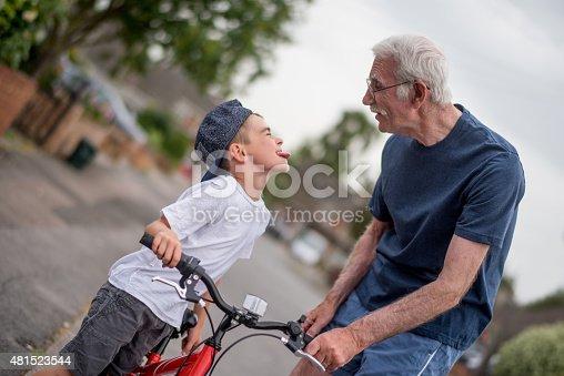 853720192 istock photo Boy making faces to his grandfather while bikw riding 481523544