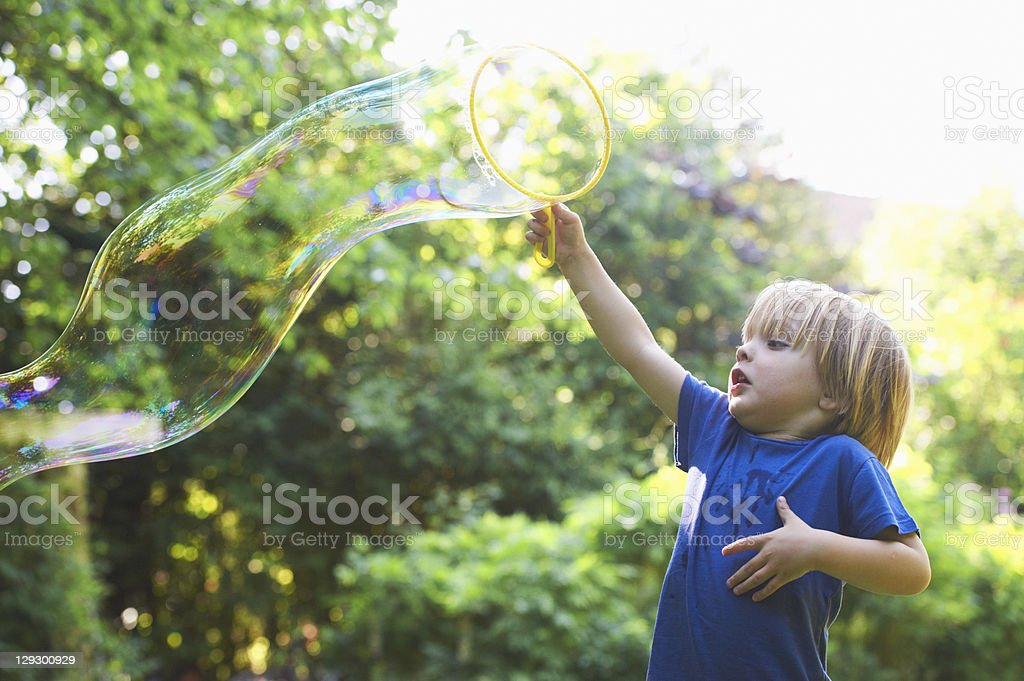 Boy making oversized bubble in backyard stock photo
