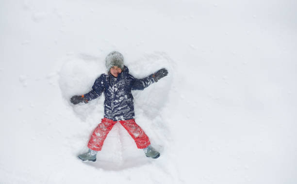 Boy making snow angel stock photo