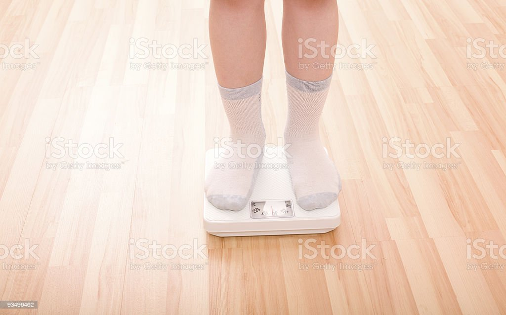 Boy measures weight on floor scales stock photo