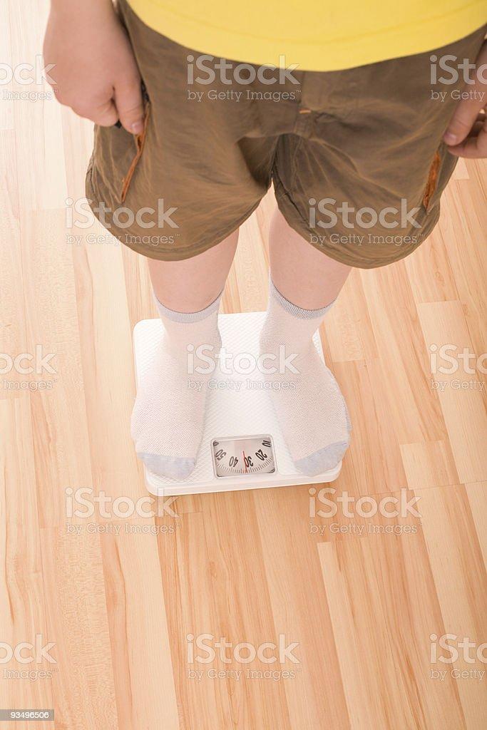 Boy measures weight on floor scales stock photo