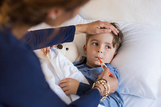 Boy measuring fever Sick boy with thermometer laying in bed and mother hand taking temperature. Mother checking temperature of her sick son who has thermometer in his mouth. Sick child with fever and illness while resting in bed. flu stock pictures, royalty-free photos & images