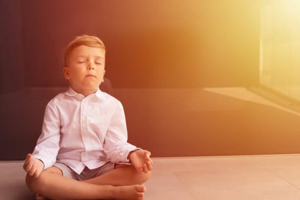 Boy meditating with eyes closed.