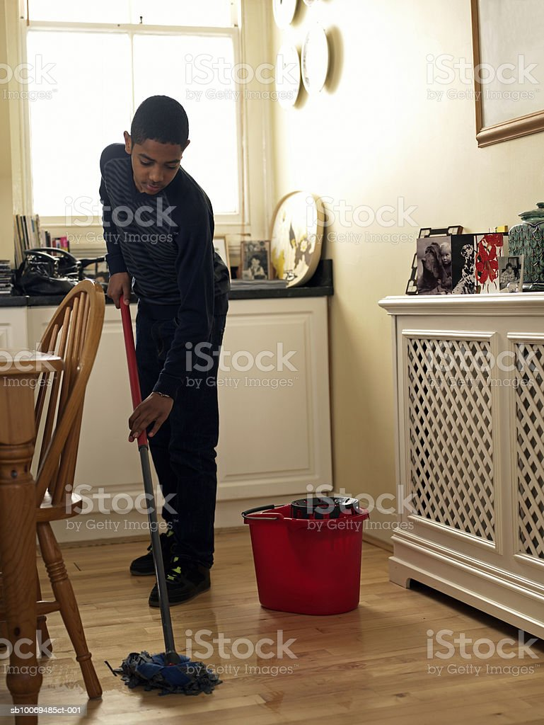 Boy (12-13) mopping floor in kitchen 免版稅 stock photo