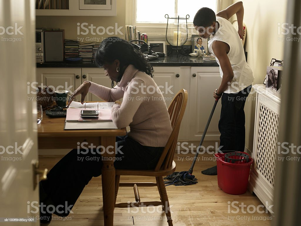 Boy (12-13) mopping kitchen floor behind mother counting bills 免版稅 stock photo