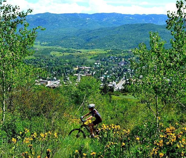 Boy Mountain Bikes Over Town A young man mountain bikes in the wildflowers above a mountain town in the Colorado Rockies. steamboat springs stock pictures, royalty-free photos & images