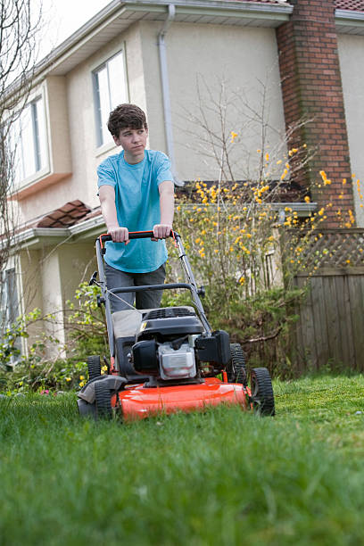 boy mows the front lawn - household chores stock photos and pictures