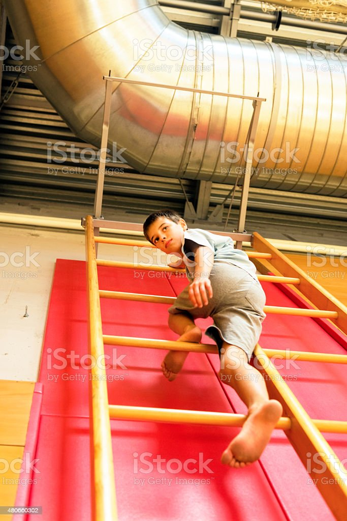 Garçon de onze gymnastique d'escalade échelle au gymnase, l'Europe - Photo