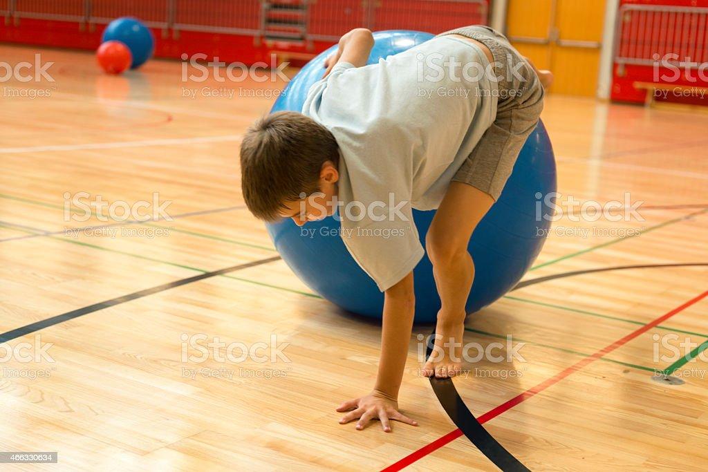 Ragazzo di undici giocando con blu Pallone per Fitness, centro sportivo scolastico - foto stock