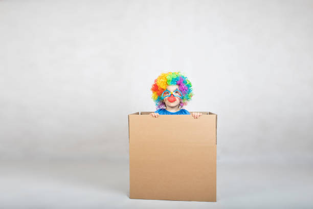 Boy of five years dressed in the costume of a clown stays in a carton paper box. stock photo