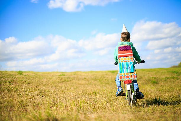 boy on a bicycle with a pile of gifts stock photo