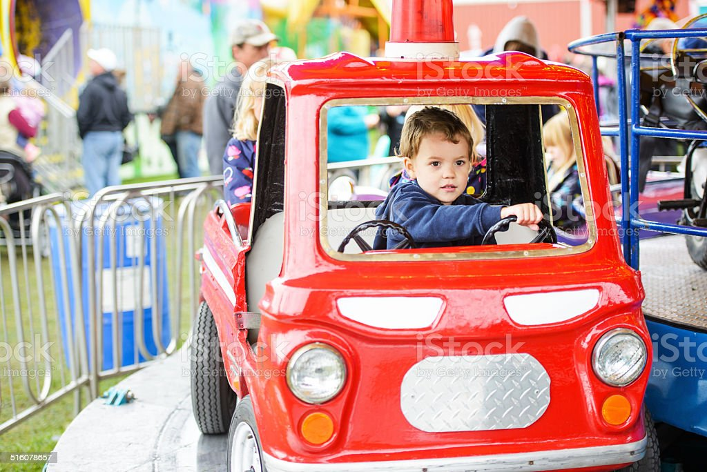 Boy on a Merry-Go-Round Firetruck stock photo