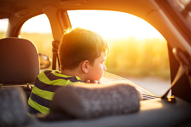 boy on a road trip - boy looking out window stock pictures, royalty-free photos & images