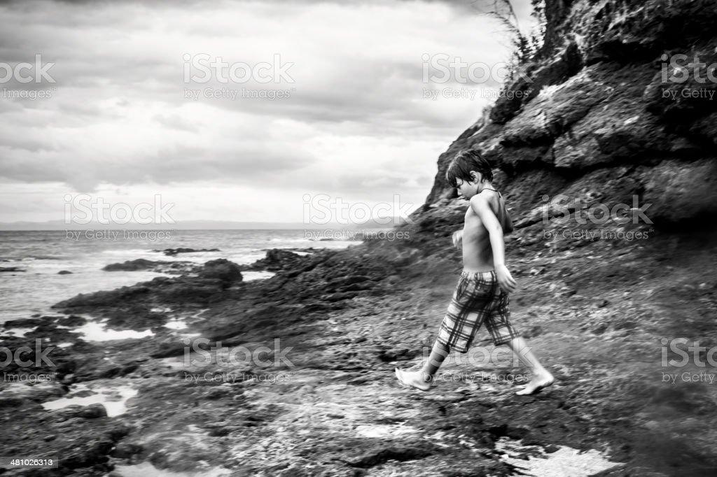 Boy on a rocky shoreline stock photo