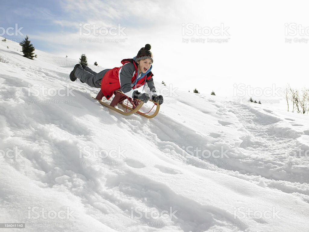 Boy On A Sled Playing In The Snow stock photo