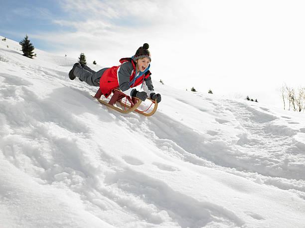 Junge auf einem Schlitten Spielen im Schnee – Foto