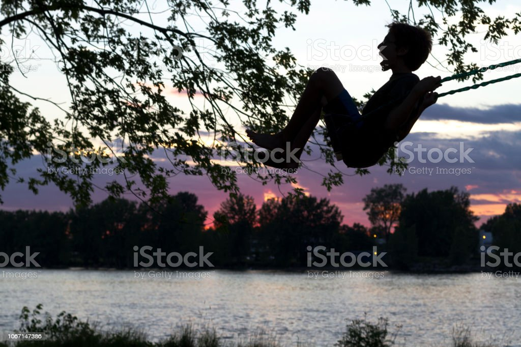 A boy on a swing at sunset stock photo