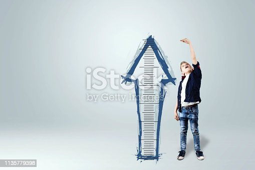 istock A boy on a white background shows how he grew up, dreams of becoming an adult. The concept of big growth, business, maturing. 1135779398