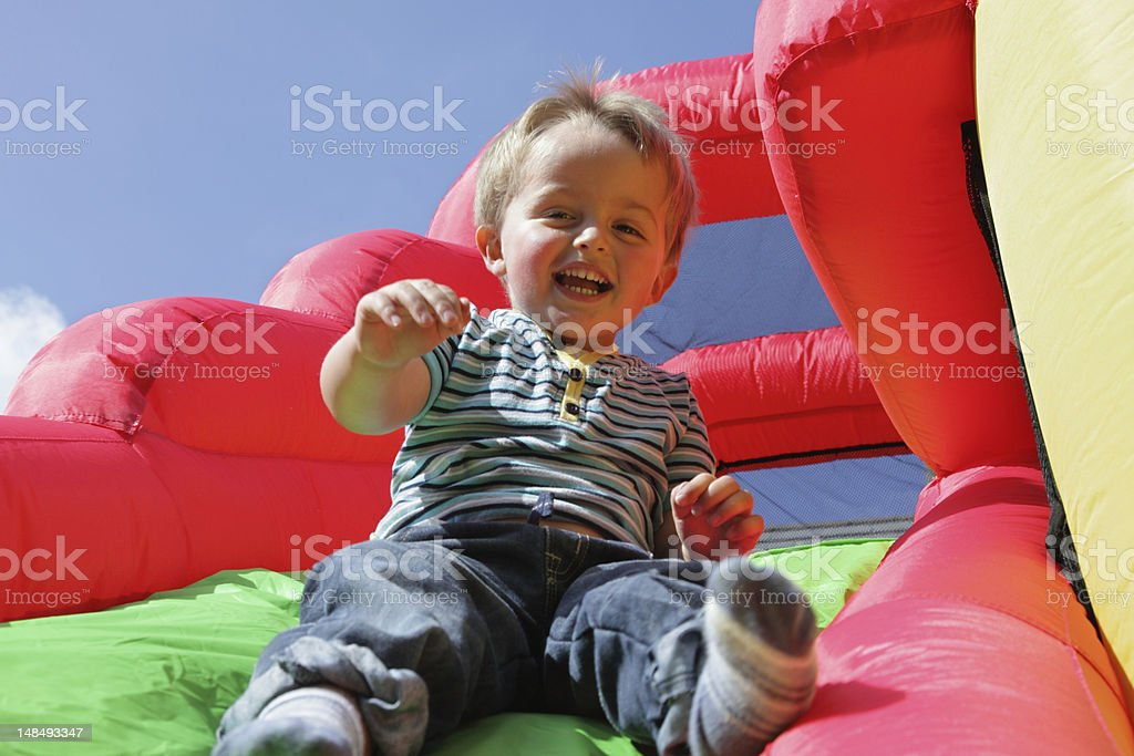 A boy on an inflatable bouncy slide stock photo