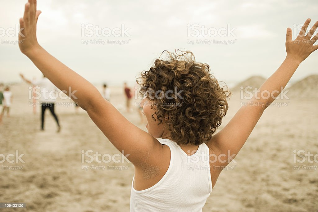 Boy on beach, arms out royalty-free stock photo