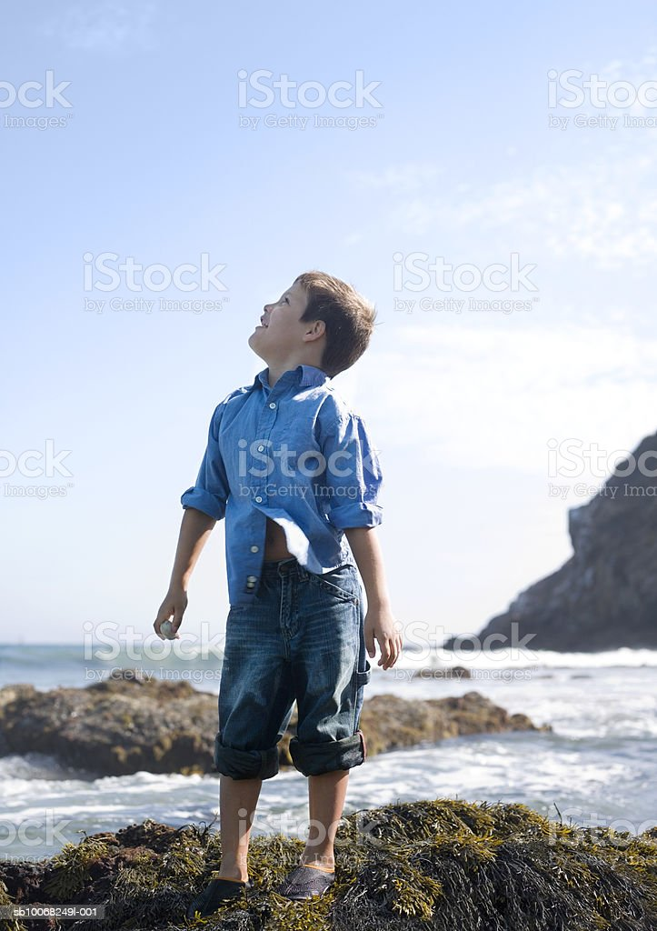Boy (6-7) on beach, looking up at sky royalty-free stock photo