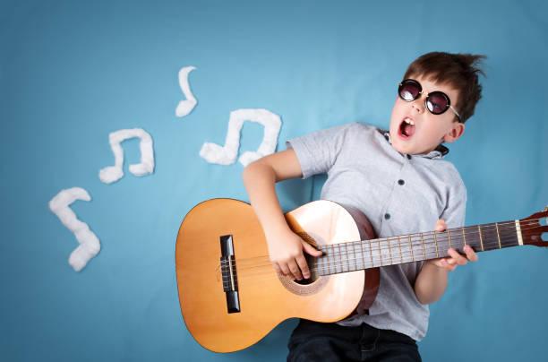 jungen auf blaue decke hintergrund mit gitarre - one song training stock-fotos und bilder