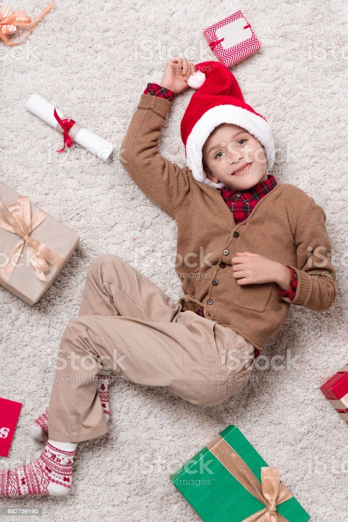 boy on carpet with christmas gifts stock photo