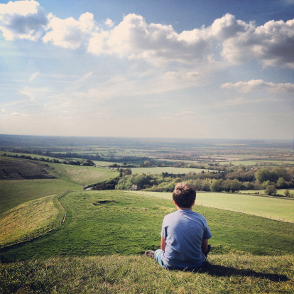 Boy sitting on the hill at White Horse Uffington, seeming lost in thought.