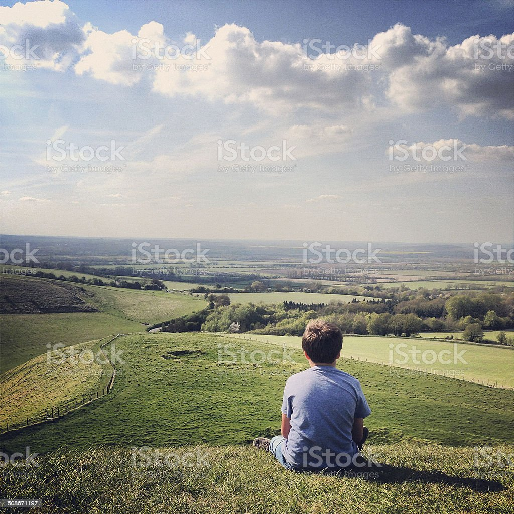 Boy on hill lost in thought stock photo