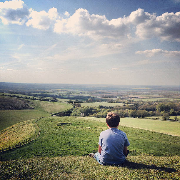 Boy on hill lost in thought Boy sitting on the hill at White Horse Uffington, seeming lost in thought. taken on mobile device stock pictures, royalty-free photos & images