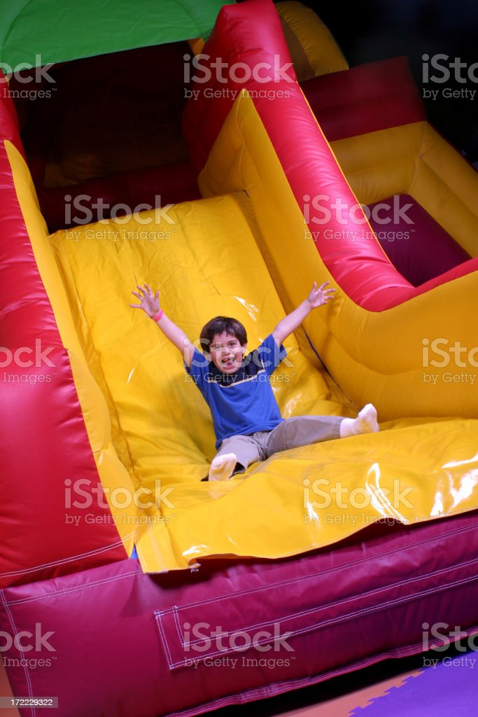 Boy on inflatable slide goes fast stock photo