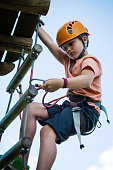Boy on ladder going down with the helmet in adventure park , ropes course
