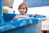 Little boy is enjoying on playground slide