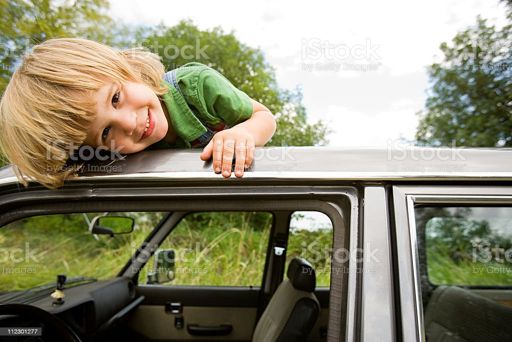 Boy on roof of car stock photo