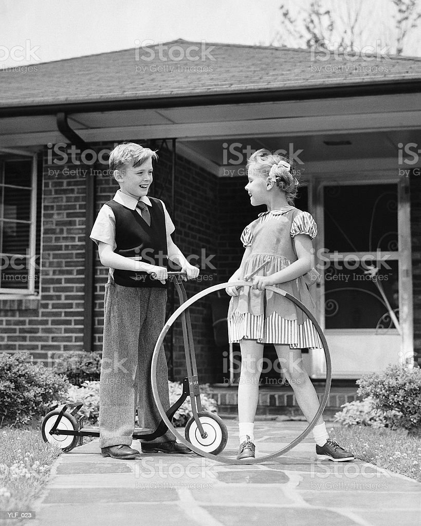 Boy on scooter, girl holding stick and hoop, outdoors royalty-free stock photo