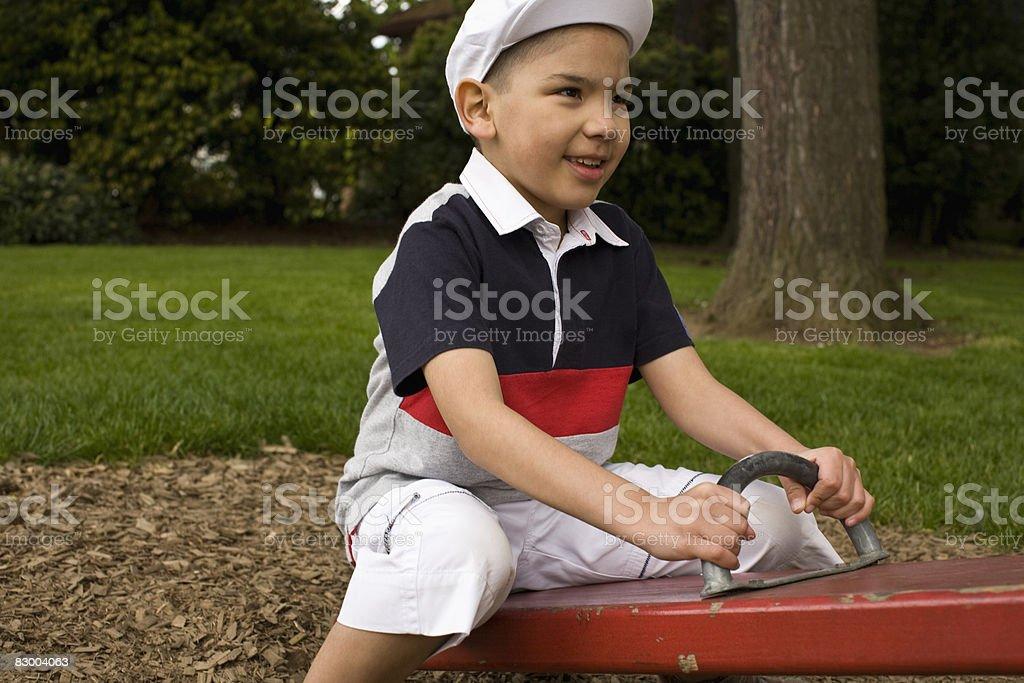 Boy on see saw royaltyfri bildbanksbilder