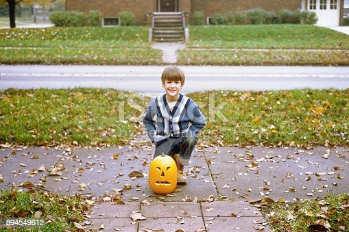 Boy in blue striped sweater kneeling on sidewalk behind jack 'o lantern. Autumn leaves on grass, sidewalk and street. Scanned film.