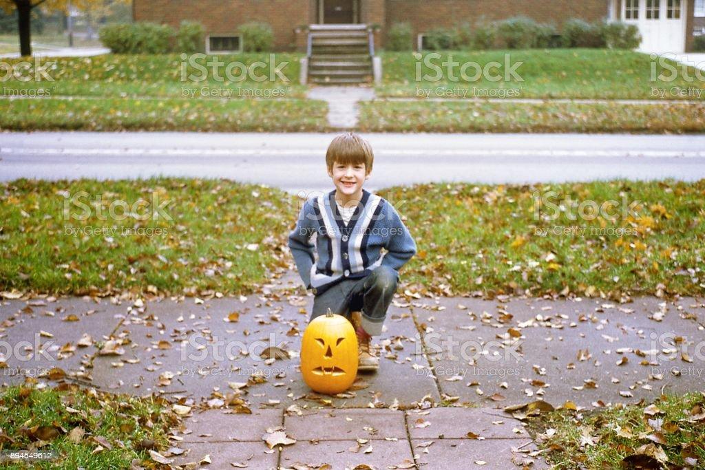 Boy on sidewalk with jack 'o lantern in suburban neighborhood 1971 stock photo