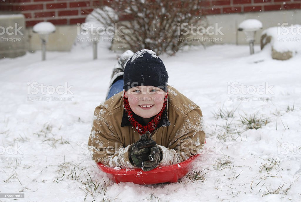 Boy on Sled in Winter stock photo