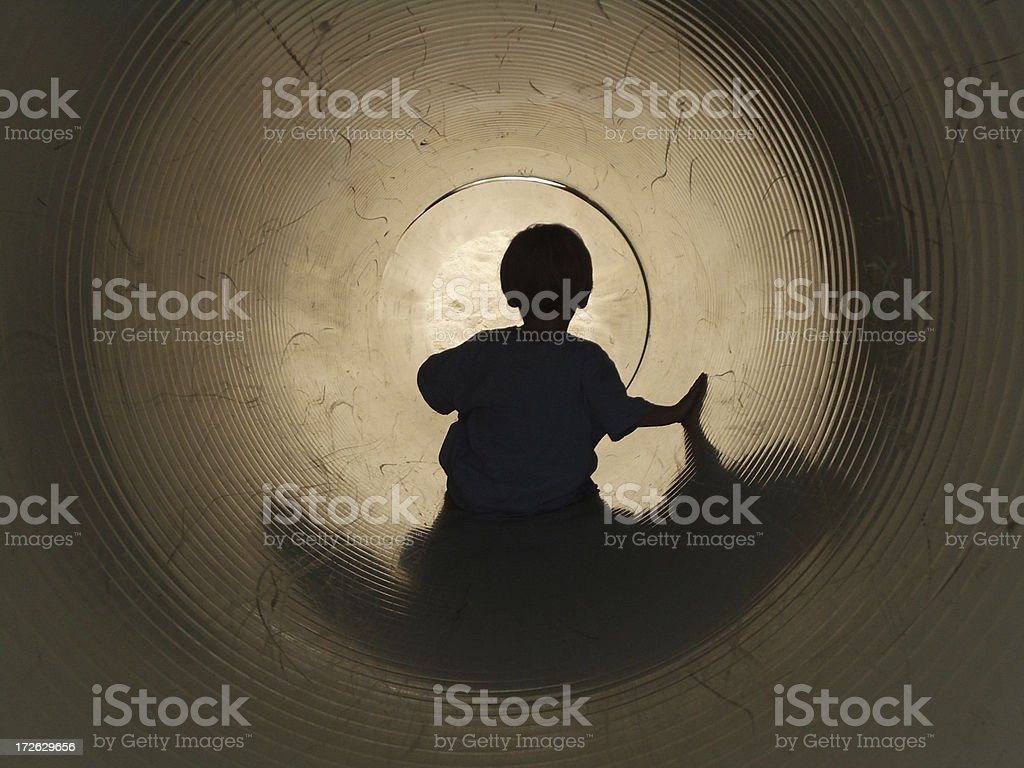 Boy on Slide: At The End of a Tunnel stock photo