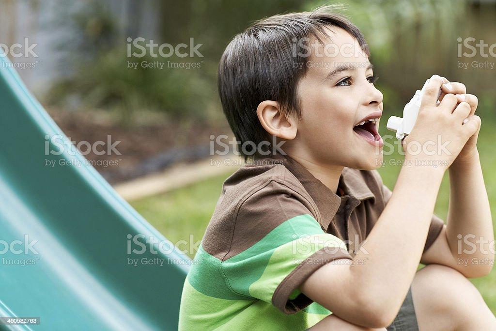Boy On Slide Using Inhaler In Park stock photo