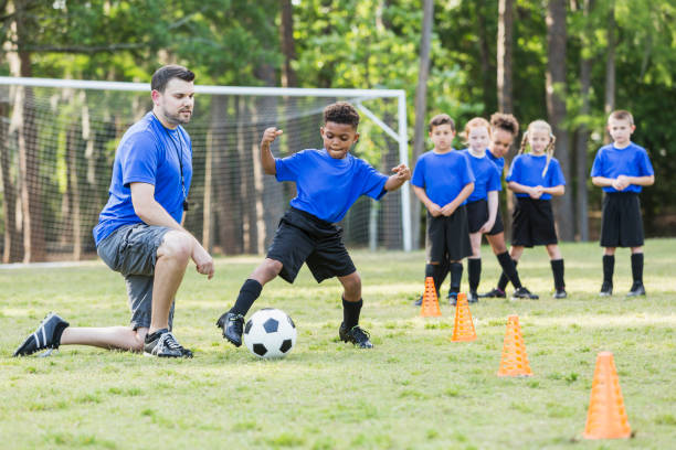 Boy on soccer team practicing, coach watching stock photo