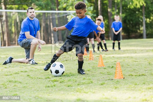 A 7 year old African-American boy on a soccer team at practicing, kicking a ball around cones. The coach is watching and other children are waiting their turn to do the drill.