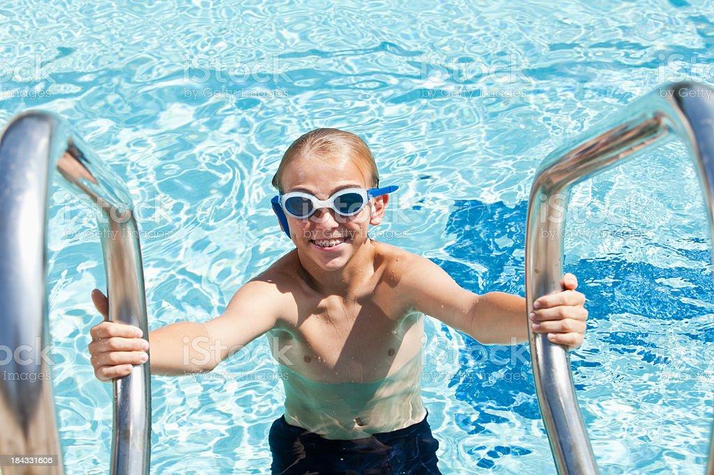 Boy on swimming pool ladder stock photo