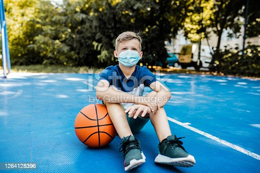 Portrait of a young boy sitting on the basketball field with a ball and wearing a mask