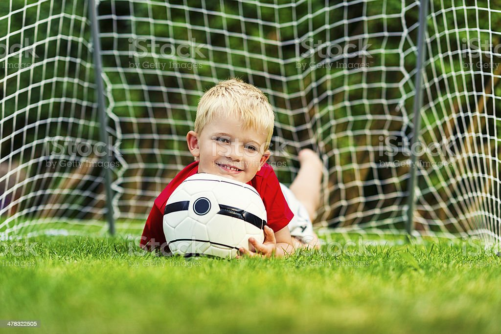 Boy on the grass holding a soccer ball royalty-free stock photo