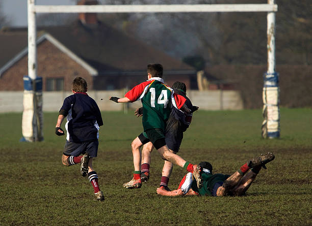 boy sobre el terreno en un juego de rugby - rugby fotografías e imágenes de stock