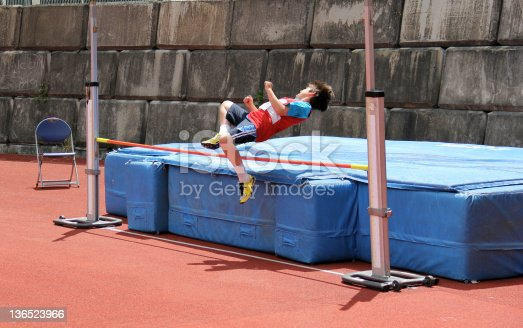 Boy compete in the high jump.
