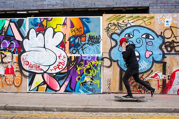 少年 電話でスケートボードに乗る前にグラフィティ - street graffiti ストックフォトと画像